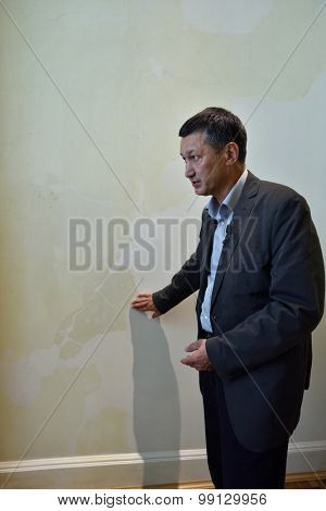 ST. PETERSBURG, RUSSIA - AUGUST 13, 2015: Director of the architectural Bureau Rafael Dayanov shows the fragment of artificial marble in the restored interiors of the Marble Palace
