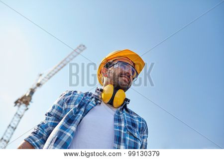 building and people concept - smiling builder with hardhat and headphones over blue sky and construction crane