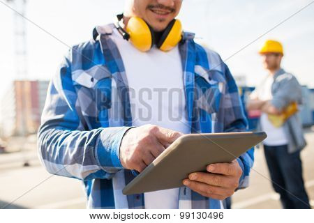 building, technology and people concept - close up of smiling builder with headphones and tablet pc computer outdoors