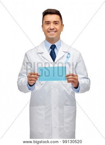 healthcare, advertisement, people and medicine concept - smiling male doctor in white coat with sky blue prostate cancer awareness ribbon holding blank paper