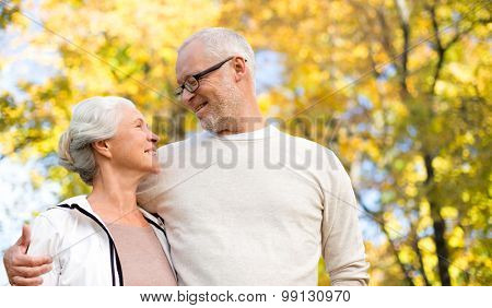 family, age, season and people concept - happy senior couple over autumn trees background