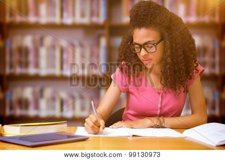 Student sitting in library writing against books on desk in library