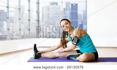 fitness, sport, training, technology and people concept - smiling woman with smartphone and earphones listening to music and stretching leg on exercise mat over gym background