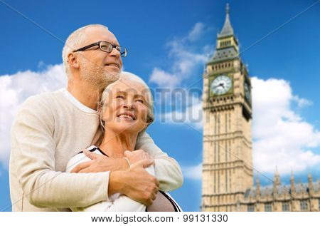 family, age, tourism, travel and people concept - happy senior couple hugging over big ben clock tower in london