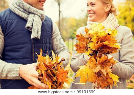 love, relationship, family, season and people concept - close up of happy smiling couple with pile of maple leaves having fun in autumn park