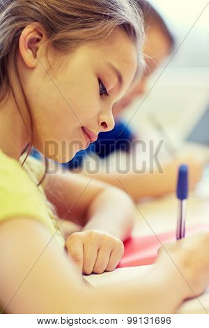 education, elementary school, learning and people concept - close up of school kids with pens and notebooks writing test in classroom