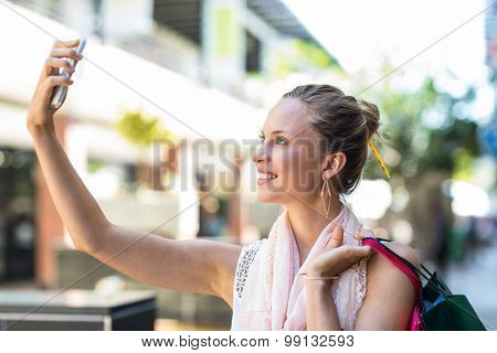 Young woman taking a selfie with her shopping bags in the mall