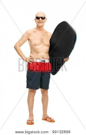 Full length portrait of a senior man in blue swim trunks holding a surfboard and looking at the camera isolated on white background