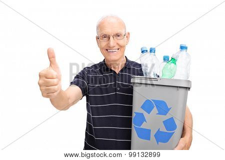 Cheerful senior holding a recycle bin full of plastic bottles and giving a thumb up isolated on white background