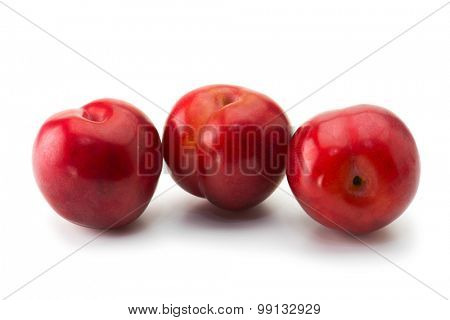 Ripe fresh harvested plums, isolated on white. Five red plums on white surface.