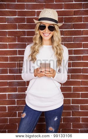 Gorgeous blonde hipster with sunglasses using smartphone against red brick background