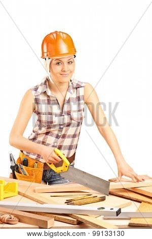 Vertical shot of a female carpenter with an orange helmet cutting a wooden plank with a handsaw isolated on white background