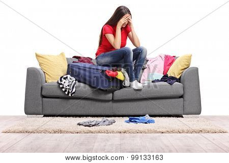 Sad young woman sitting on a suitcase full of clothes and looking down isolated on white background