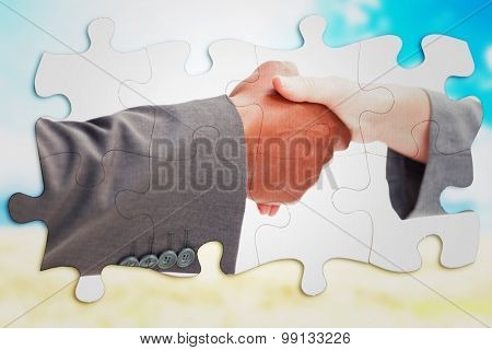 Business handshake against blue sky over fields