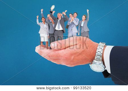 Excited business team cheering at camera with trophy against blue background