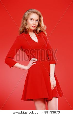 Beautiful young woman in red dress and with blonde curled hair. Beauty, fashion. Cosmetics, make-up. Red background.