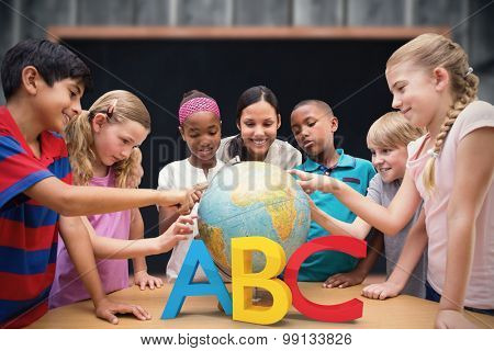 Cute pupils and teacher looking at globe in library against blackboard with copy space on wooden board