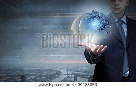 Close up of businessman holding human brain with working gears