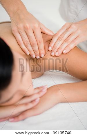 Pretty brunette enjoying a massage at the health spa