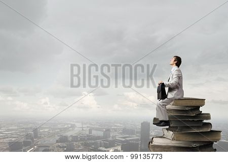 Young businessman with suitcase sitting on pile of old books