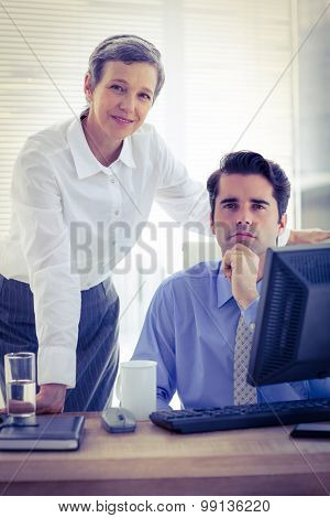 Portrait of two colleagues working together on computer at the office