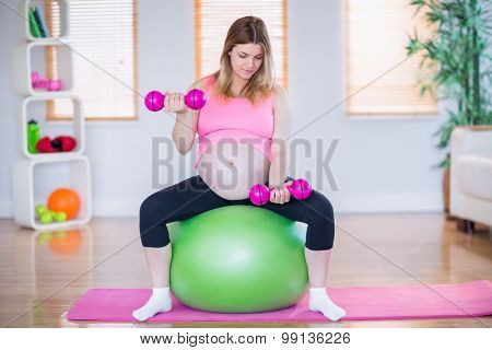 Pregnant woman lifting dumbbells on exercise ball in the living room
