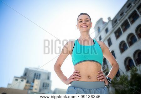 Portrait of a beautiful athlete with her hands on her hips on a sunny day