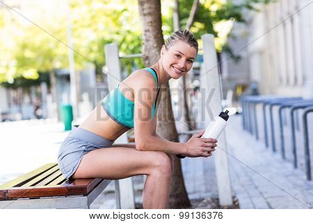 A beautiful woman sitting and holding a bottle on a sunny day