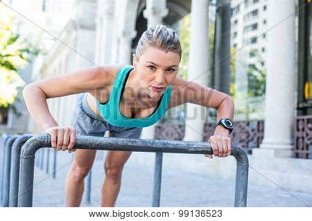 A beautiful woman stretching her body against pipes on a sunny day