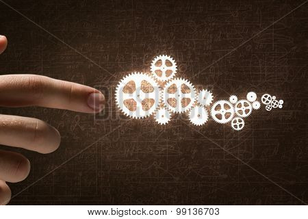 Close up of hand and gears mechanism on sketches background