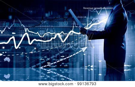 Side view of businessman with papers in hand and diagrams on virtual panel