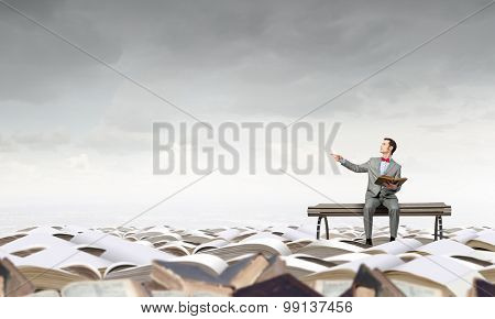 Young businessman sitting on bench with book in hands and pointing with finger