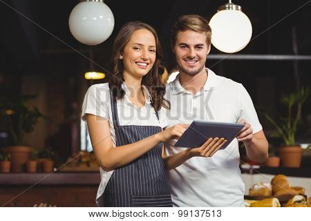 Portrait of co-workers holding a tablet at the coffee shop