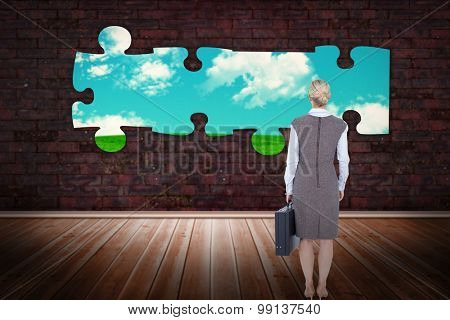 Back turned businesswoman holding a briefcase against green field under blue sky