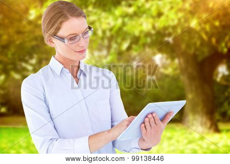 Businesswoman using tablet pc against trees and meadow in the park