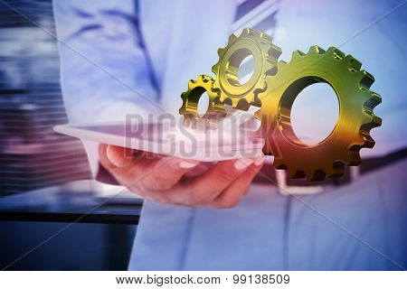 Close up view of businessman using tablet computer against metal cog and wheel connecting