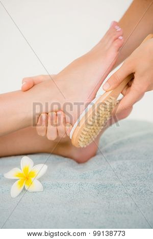 Close up side view of a young woman receiving pedicure treatment at spa center