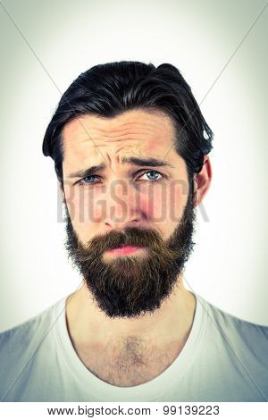 Handsome hipster frowning at camera on vignette background