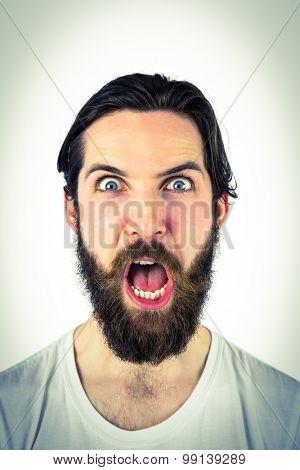 Handsome hipster shouting at camera on vignette background