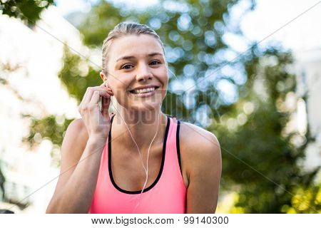 Portrait of a beautiful athlete putting her headphones on a sunny day
