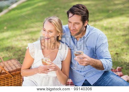 Couple on date holding a glass of white wine and looking away