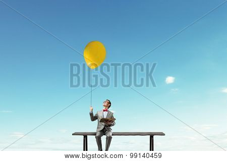Young businessman sitting on bench with balloon in one hand and book in other
