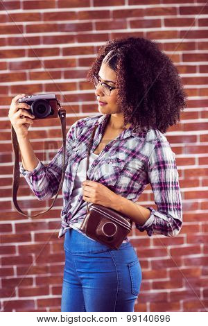 Attractive hipster holding camera and looking at it against red brick background