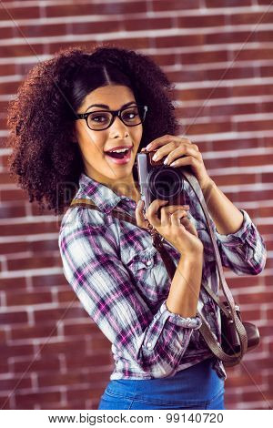 Portrait of attractive hipster photographing towards camera against red brick background