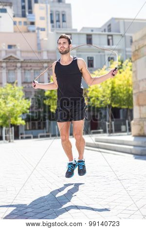 Handsome athlete doing jumping rope on a sunny day