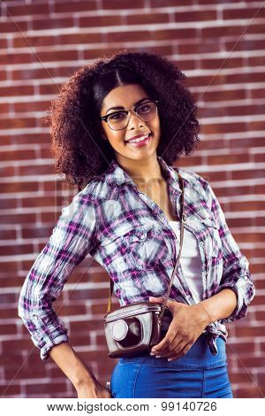 Portrait of attractive smiling hipster posing with camera against red brick background