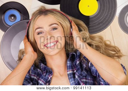 Portrait of a beautiful woman with headphones lying against vinyl