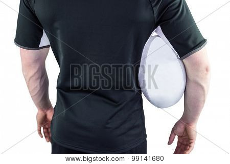 Back view of a rugby player holding a rugby ball