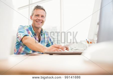Portrait of smiling casual designer working with computer in the office