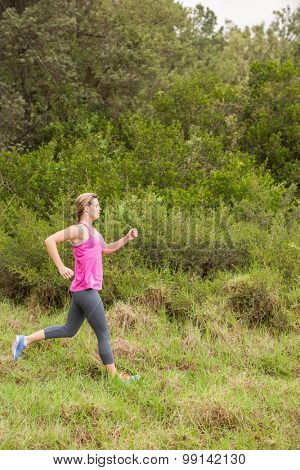 Pretty blonde athlete jogging in the nature